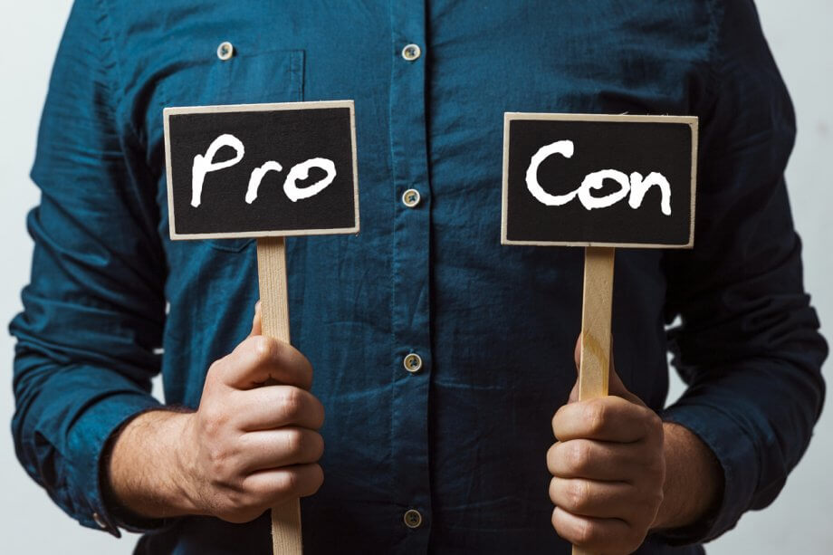 "Photograph of a man holding two small signs in each hand. One sign says ""Pro"" the other sign says ""Con""."
